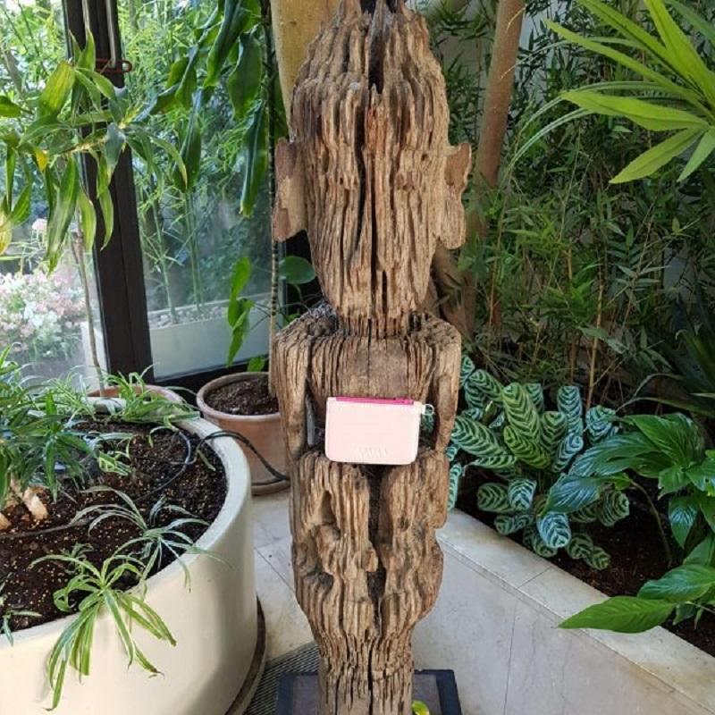 Culture Shock A Wooden Carving Holding a Pink Arayla Handbag
